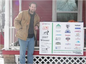 2007 Energy Makeover Winner Man Standing with coat by Red Home